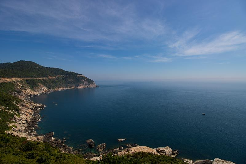 Cham Island eastern coastline with road along the cliff looking out over South China Sea
