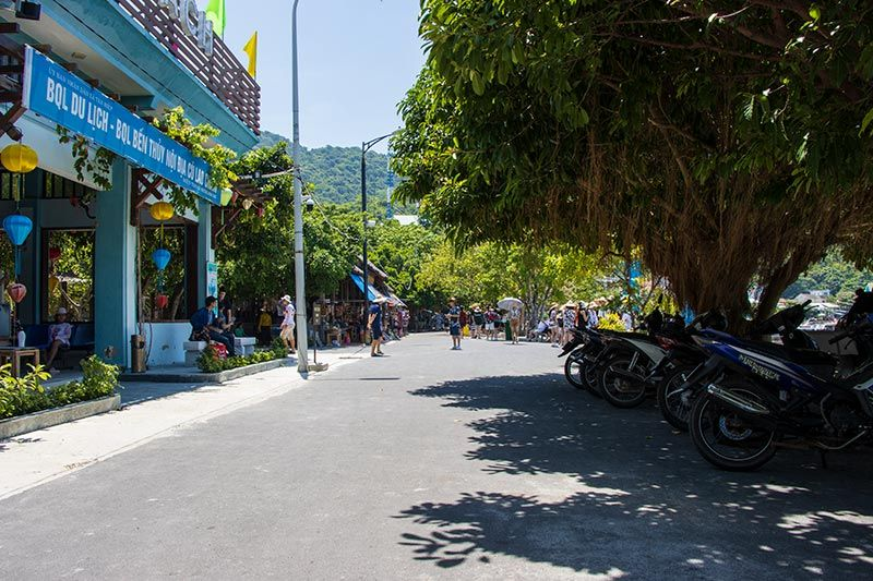 Entrance to Cham Island market across the road with scooter rental to the right
