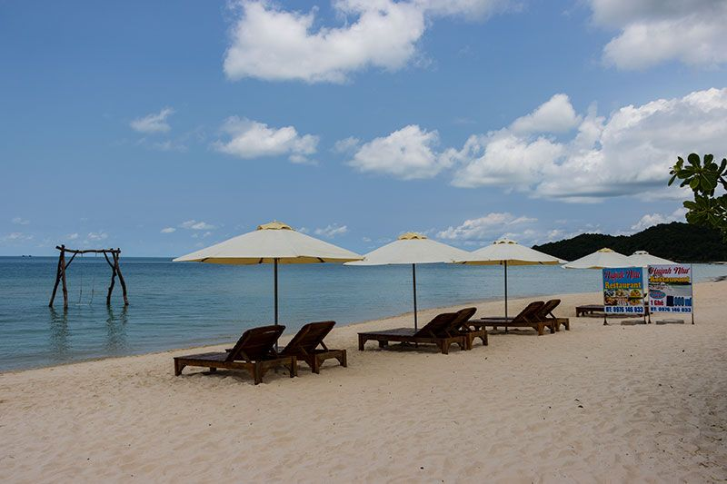 Sun loungers on Sao Beach facing the water with a wooden swing